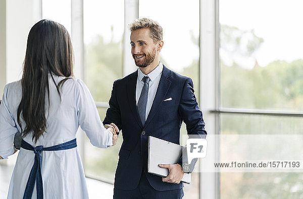 Geschäftsmann und Geschäftsfrau beim Händeschütteln am Fenster