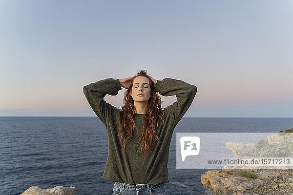 Rothaarige junge Frau bei Sonnenuntergang an der Küste  Ibiza  Spanien