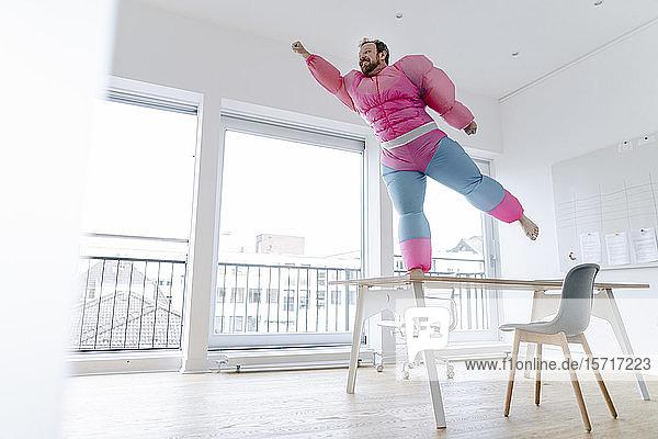 Businessman in office wearing pink bodybuilder costume pretending to fly