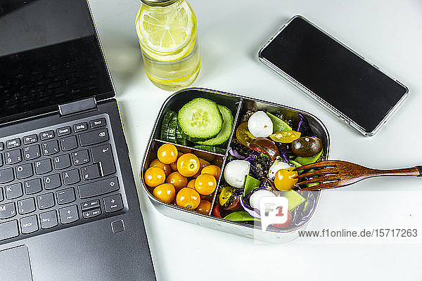 Laptop  smart phone  bottle of lemonade and lunchbox with cucumber slices  winter cherries and quinoa salad (quinoa  cherry tomato  red cabbage  sugar snap peas and mozzarella balls)