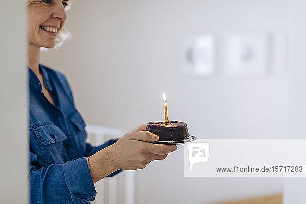 Glückliche reife Frau mit Geburtstagskuchen zu Hause Glückliche reife Frau mit Geburtstagskuchen zu Hause