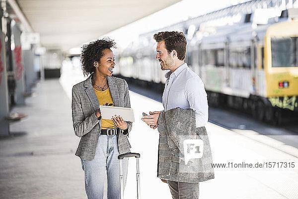 Junger Geschäftsmann und glückliche Geschäftsfrau benutzen gemeinsam Tabletten am Bahnhof