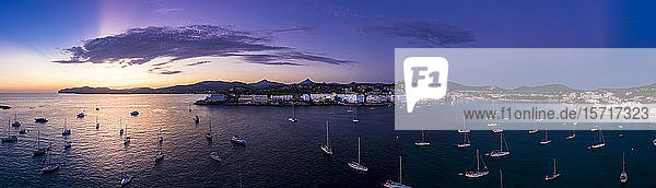 Spain  Mallorca  Santa Ponsa  Aerial panorama of boats floating in coastal water at purple dusk with town in background
