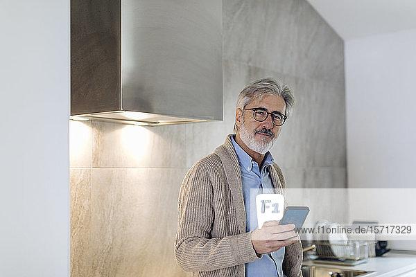 Porträt eines reifen Mannes mit Handy in der heimischen Küche Porträt eines reifen Mannes mit Handy in der heimischen Küche