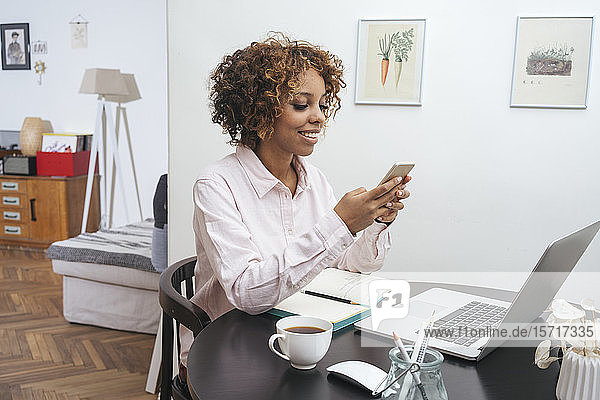 Young woman sitting at table at home using smartphone