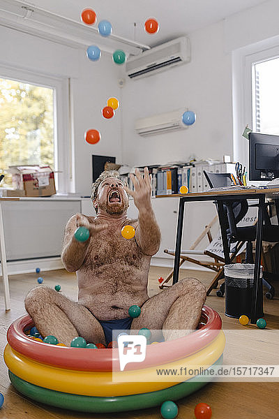 Crazy businessman sitting in wading pool in office playing with balls