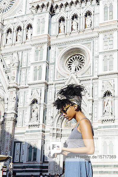 Young woman with camera standing in front of cathedral  Florence  Italy