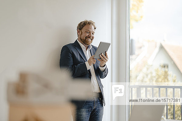Smiling businessman using tablet at the window