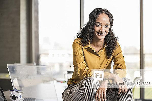 Porträt einer lächelnden jungen Geschäftsfrau  die im Büro auf dem Schreibtisch sitzt