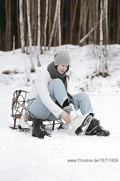 Frau zieht Schlittschuhe auf Schneefeld an
