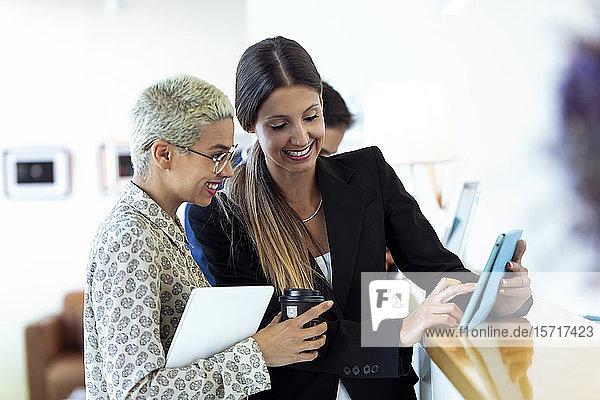 Zwei lächelnde Geschäftsfrauen mit Kaffee und Tablette zum Mitnehmen am Empfang