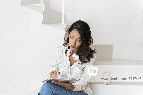 Porträt eines jungen Architekten  der auf Stufen in einem Atelier sitzt und an einem Tablett arbeitet