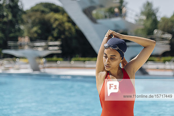 Portrait of young woman with swimming cap and goggles in red bathsuit stretching in front of pool
