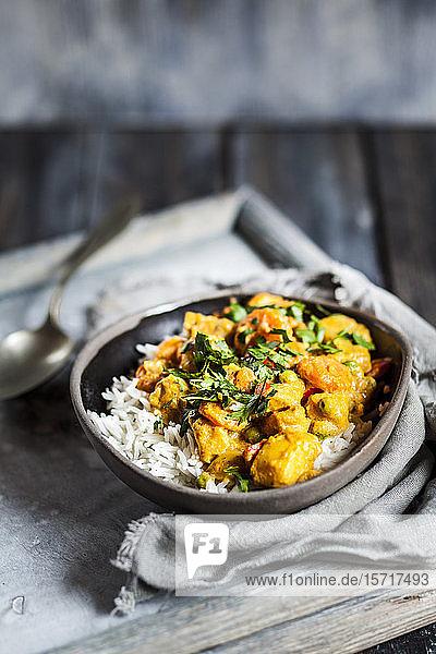 Schale mit veganem Curry mit Kartoffeln,  Karotten,  Erbsen,  Petersilie und Kürbis