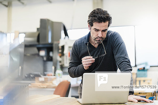 Businessman using laptop in a factory