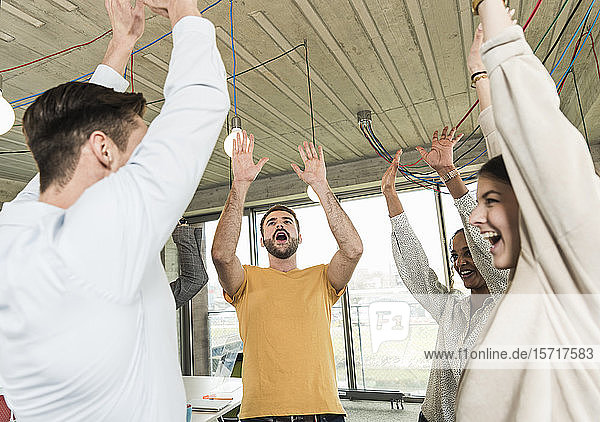Happy young business people raising their arms in office