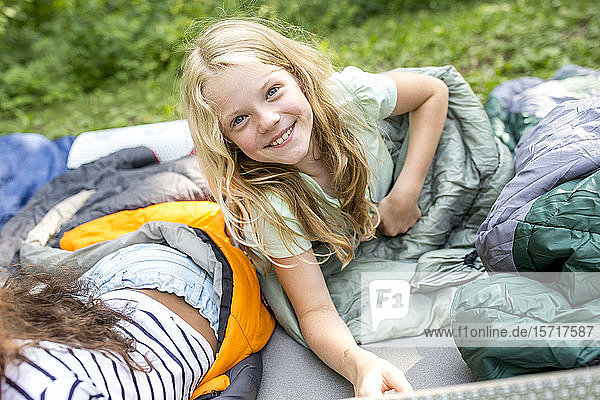 Kleines Mädchen liegt auf einem Schlafsack und schaut in die Kamera