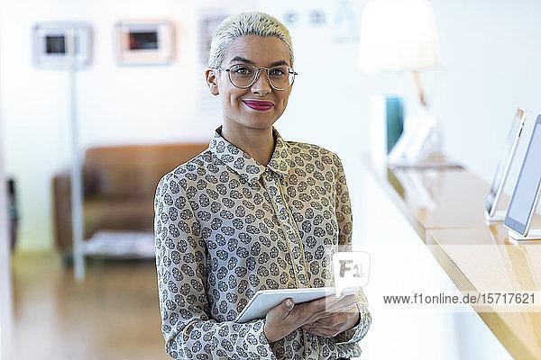 Porträt einer selbstbewussten Geschäftsfrau  die ein Tablett im Amt hält
