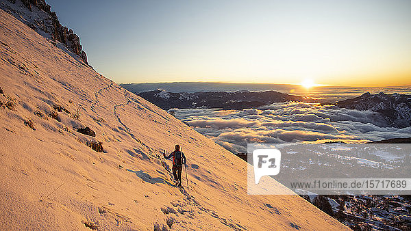 Mountaineer on the mountainside during sunrise  Orobie Alps  Lecco  Italy