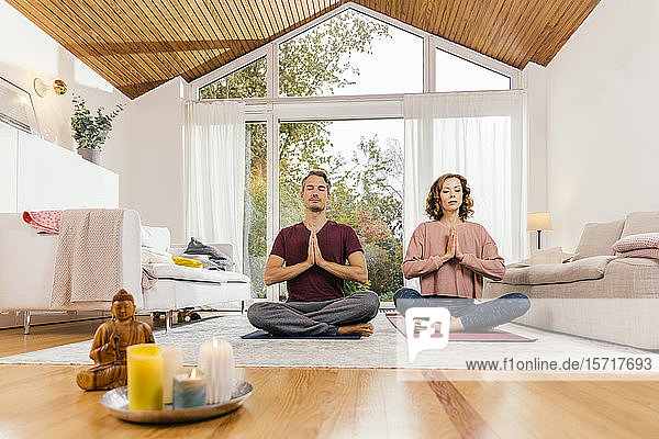 Couple meditating together at home