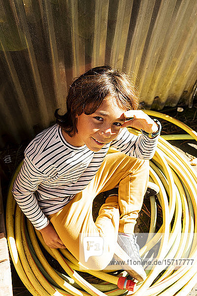 Portrait of smiling boy sitting among rolled up garden hose at plant nursery