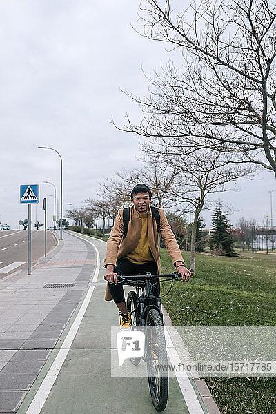 Porträt eines lächelnden jungen Mannes beim Fahrradfahren in der Stadt
