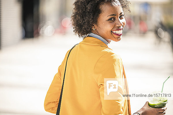 Portrait of happy young woman with smoothie in the city  Lisbon  Portugal