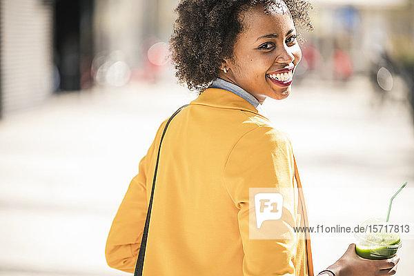 Porträt einer glücklichen jungen Frau mit Smoothie in der Stadt  Lissabon  Portugal