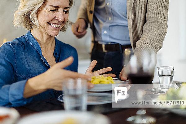 Ein reifer Mann serviert seiner Frau zu Hause in der Küche das Abendessen