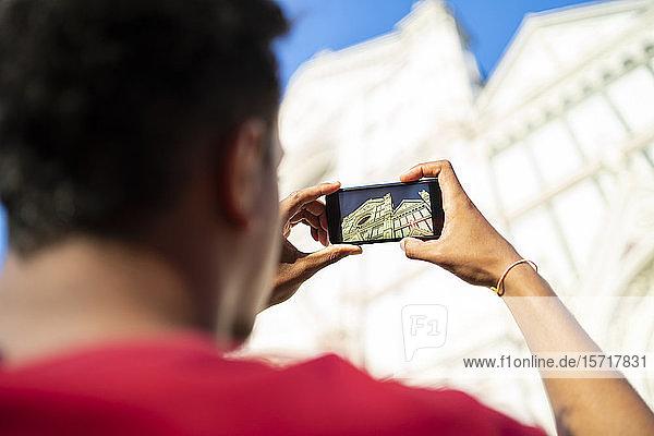 Junger Mann macht ein Smartphone-Foto von der Basilica di Santa Maria del Fiore  Florenz  Italien