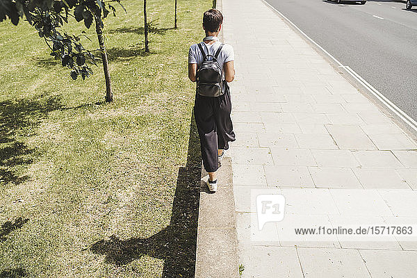 Rückenansicht einer Frau mit Rucksack  die auf einer Wand balanciert Rückenansicht einer Frau mit Rucksack, die auf einer Wand balanciert