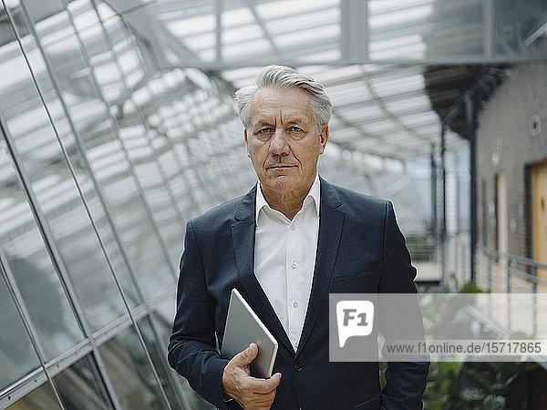 Porträt eines seriösen leitenden Geschäftsmannes mit Tablette im Amt
