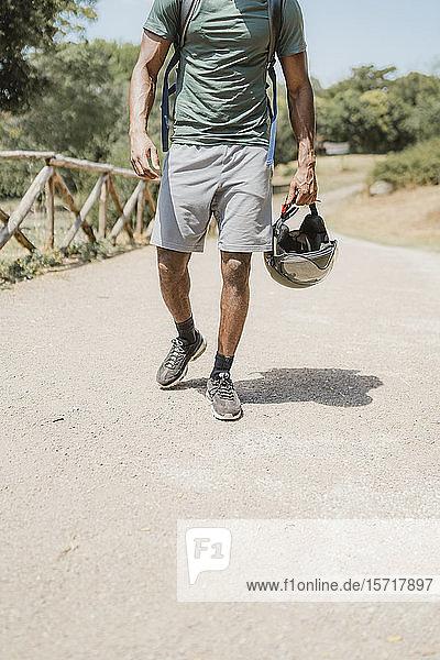 Junger Mann mit Helm geht im Park spazieren Junger Mann mit Helm geht im Park spazieren