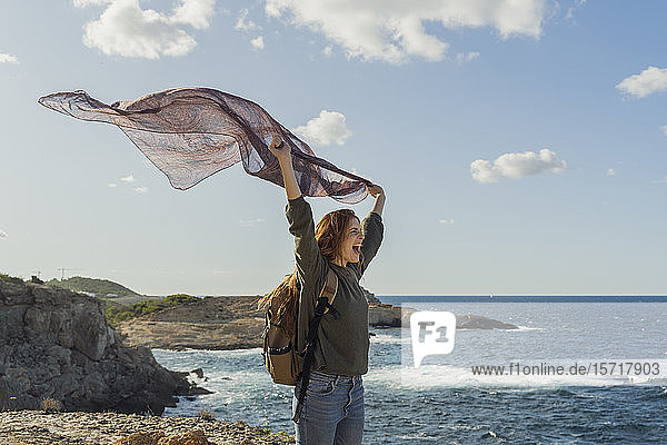 Happy redheaded young woman holding a cloth at the coast  Ibiza  Spain