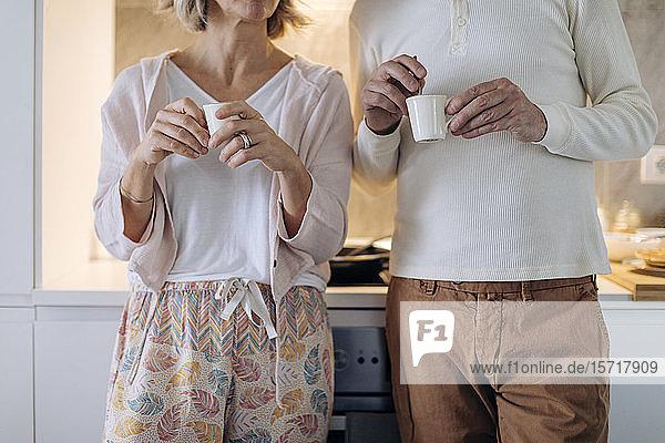 Mittelteil eines Paares  das zu Hause in der Küche Kaffee trinkt Mittelteil eines Paares, das zu Hause in der Küche Kaffee trinkt