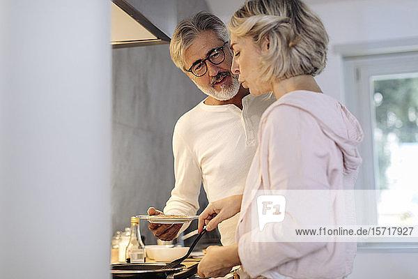 Reifes Paar bereitet zu Hause in der Küche Pfannkuchen zu Reifes Paar bereitet zu Hause in der Küche Pfannkuchen zu