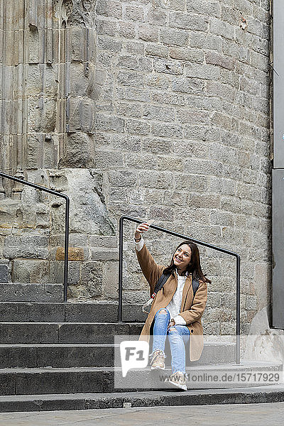 Smiling young woman sitting on stairs in the city taking a selfie  Barcelona  Spain