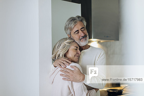 Affectionate mature couple hugging at home