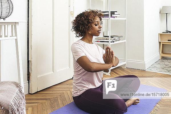 Junge Frau  die zu Hause Yoga praktiziert