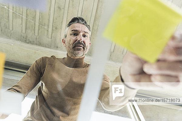 Reifer Geschäftsmann arbeitet an Haftnotizen auf Glastisch im Büro