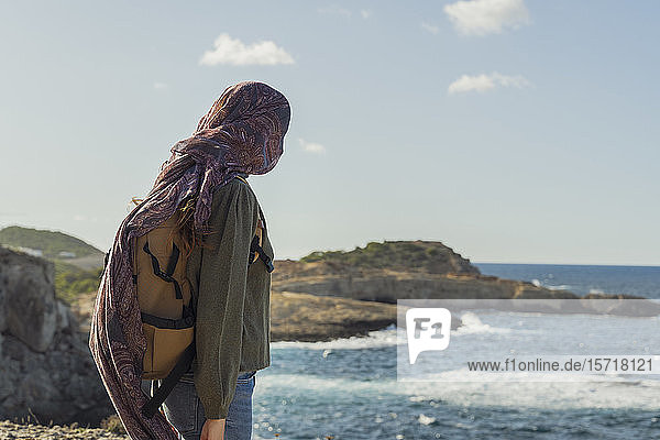 Young woman at the coast with cloth around her face  Ibiza  Spain