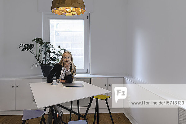 Portrait of young businesswoman sitting at table in office