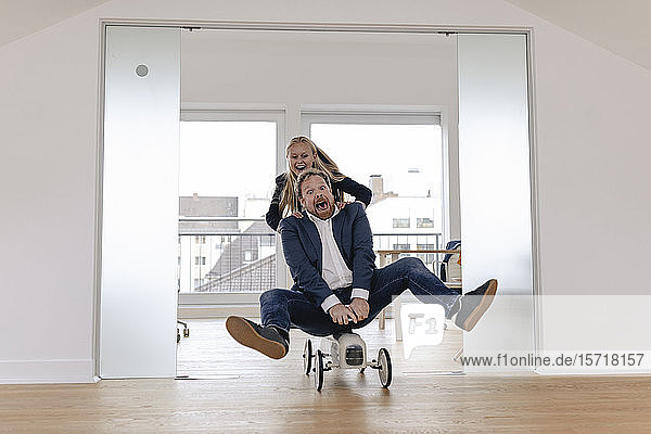 Playful businesswoman pushing businessman on toy car in office