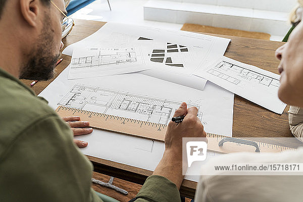 Crop view of two architects working together at desk in office