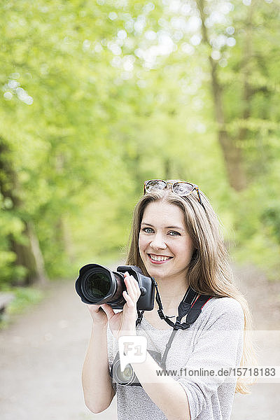 Portrait of smiling young woman comparing two different cameras outdoors