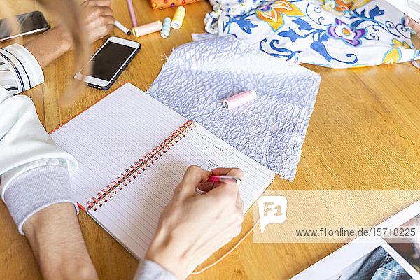 Fashion designer taking noteson desk in office