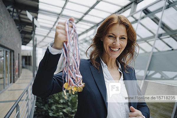 Porträt einer glücklichen Geschäftsfrau mit Medaillen im Amt