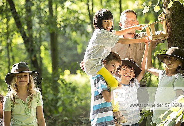 Schulkinder  die ein Bidhouse an einem Baum reparieren