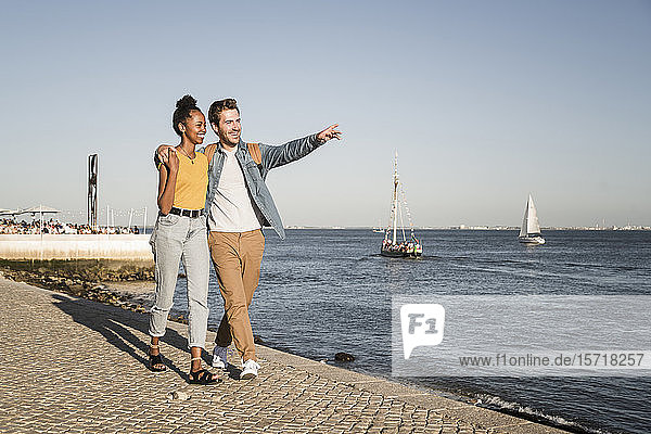 Happy young couple walking on pier at the waterfront  Lisbon  Portugal