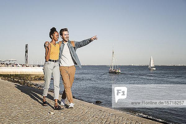 Glückliches junges Paar beim Spaziergang am Pier am Wasser  Lissabon  Portugal